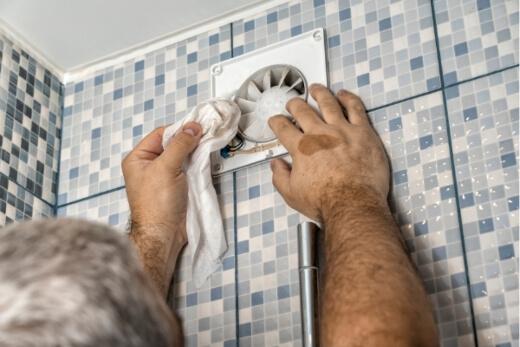 A man installing an exhaust fan